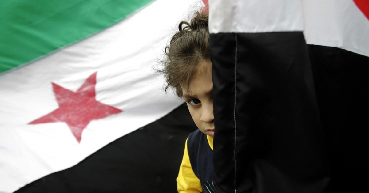 A child stands behind a Syrian flag.</p>