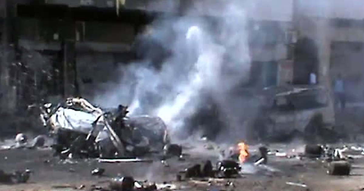 This image grab of footage uploaded on YouTube on March 20, 2012 allegedly shows a burning vehicle and gas cylinders, mainly used for cooking, strewn across a street after a mortar shell struck a gas depot store in the central Syrian city of Homs.</p>