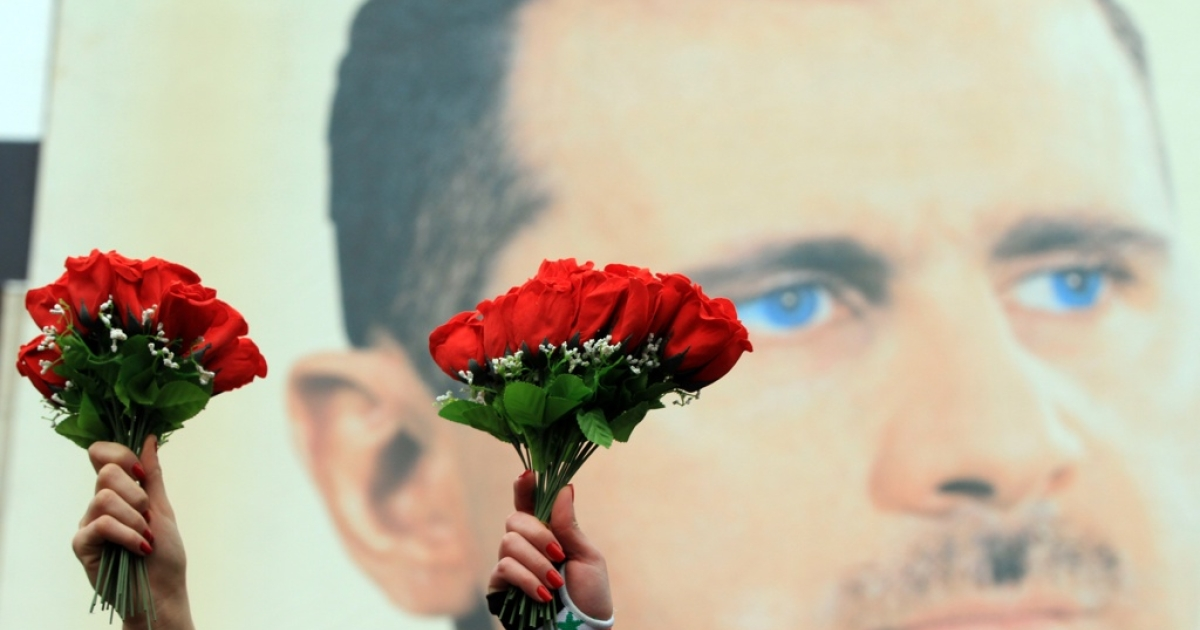 Syrian demonstrators hold up red flowers for Valentine's Day in front of a portrait of Syrian President Bashar al-Assad during a rally to show their support for their leaderin central Damascus on Feb. 14, 2012.</p>