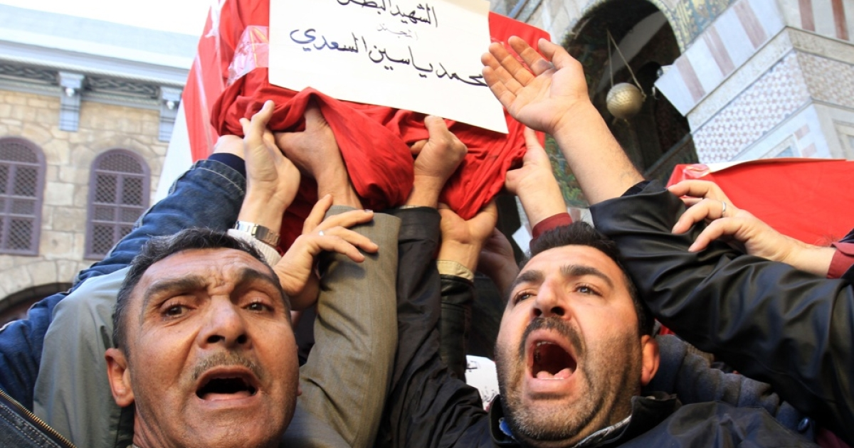 Syrian mourners carry a coffin during the mass funeral of 44 people killed in twin suicide bombings that targeted intelligence agency compounds in Damascus on Dec. 24, 2011.</p>