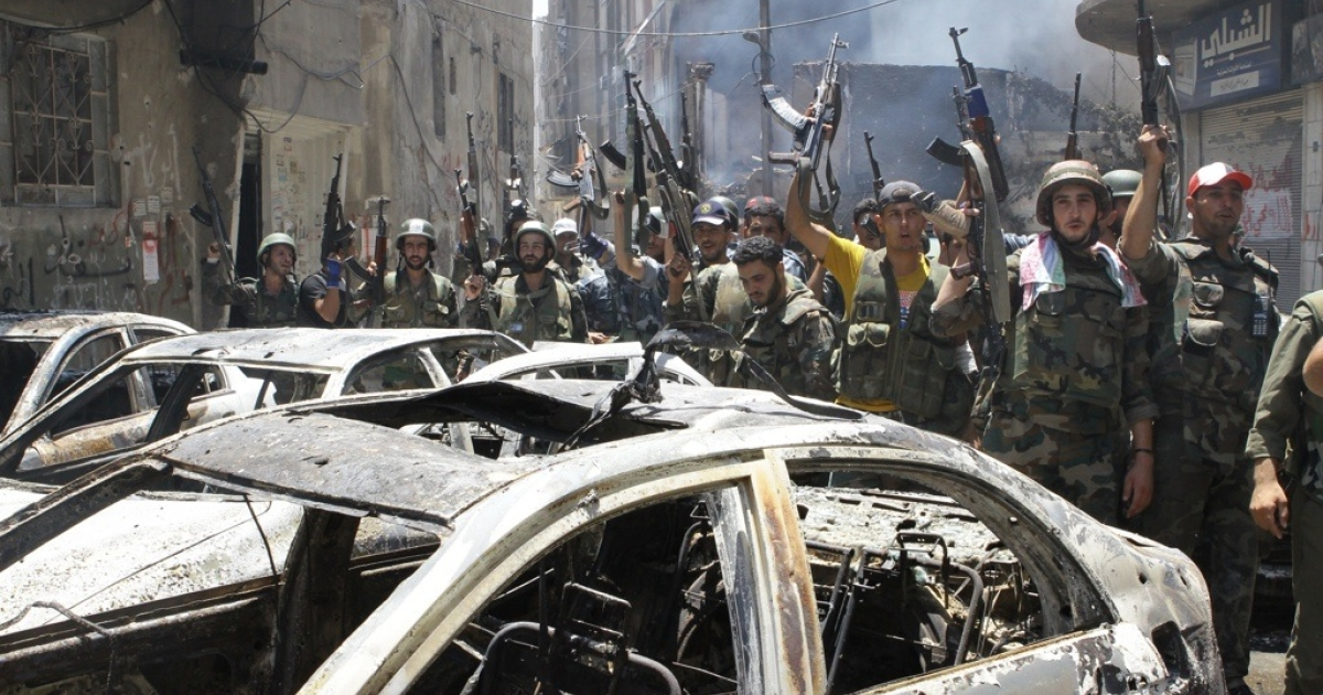 Syrian soldiers celebrate in the Midan area of Damascus on July 20, 2012. Syrian regime forces routed rebel fighters from the Damascus neighborhood, causing many residents to flee for the countryside.</p>