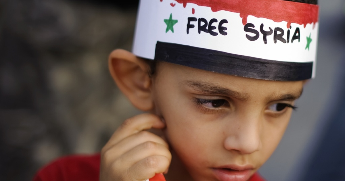 A boy wearing a headband reading 'Free Syria' looks on during a 'Jasmin march for the Syrian people's freedom' that gathered about 300 activists, including Syrians opposed to President Bashar al-Assad's regime living in Switzerland, on Sept. 17, 2011 in Geneva.</p>