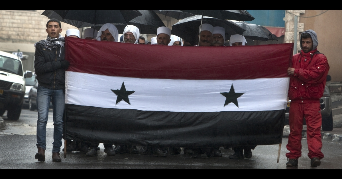 Druze residents of the Golan Heights hold Syrian flags during a rally in the Druze village of Majdal Shams on Feb. 14, 2011 in protest against the 1981 Israeli annexation of the strategic plateau. Israel captured the Golan Heights from Syria after the 1967 Arab-Israeli war.</p>