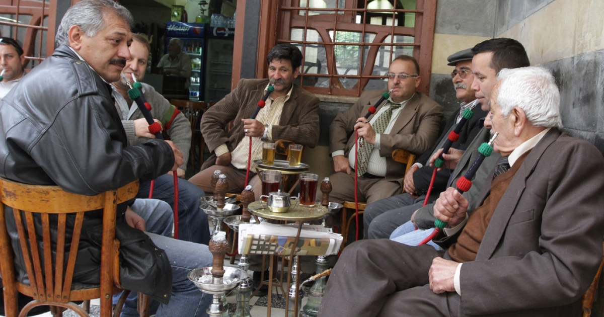Syrian men drink tea and smoke water pipes as they sit at a cafe in the capital Damascus where many people are beginning to debate their situation.</p>