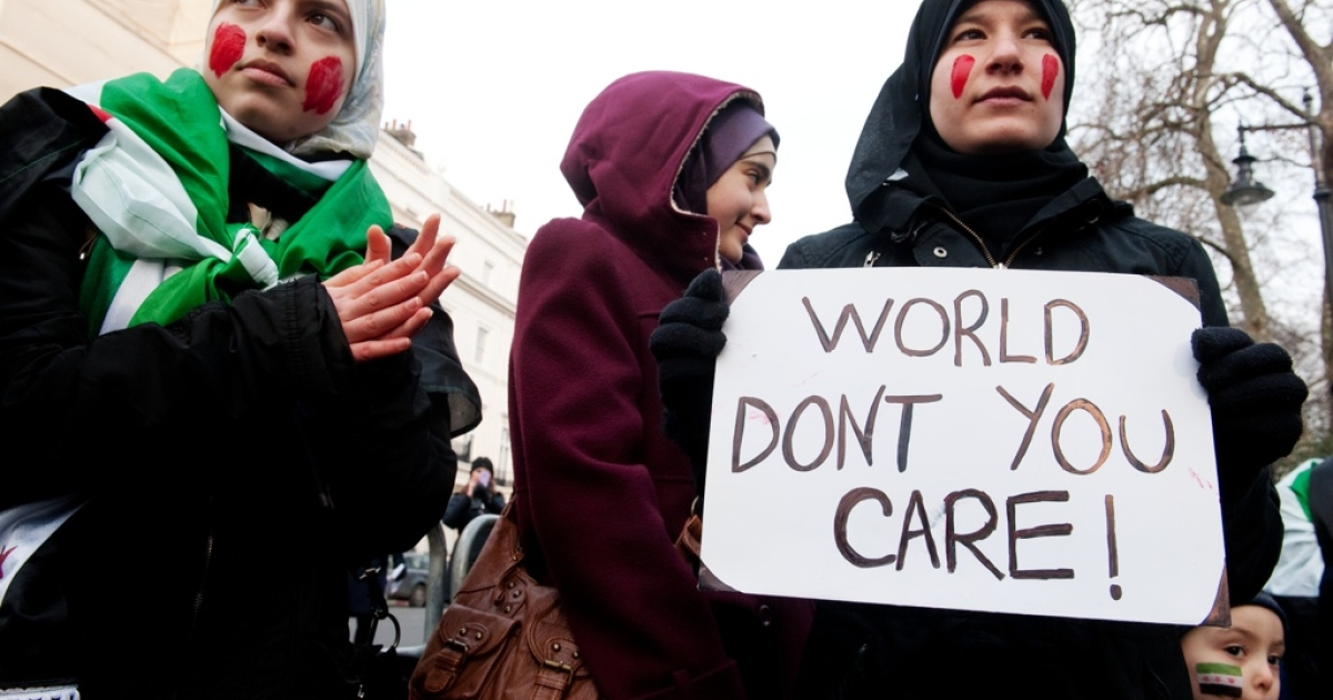 A protester holds a sign during a demonstration against the regime of Syria's president, Bashar al-Assad, and his crackdown on pro-democracy protests on Feb. 4, 2012 in London.</p>