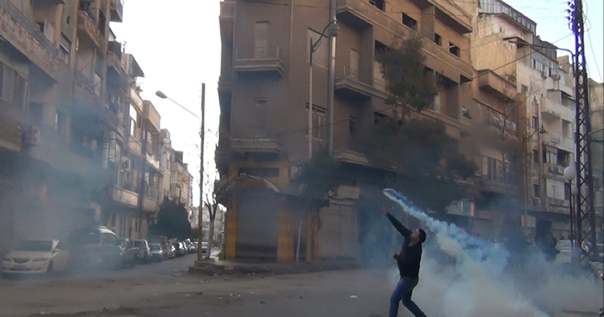 A protester in the flahspoint central Syrian city of Homs throws a tear gas bomb back towards security forces, on December 27, 2011. The commander of the rebel Free Syria Army threatened to escalate attacks against government forces if Arab League monitors did not solve the crisis in Syria.</p>