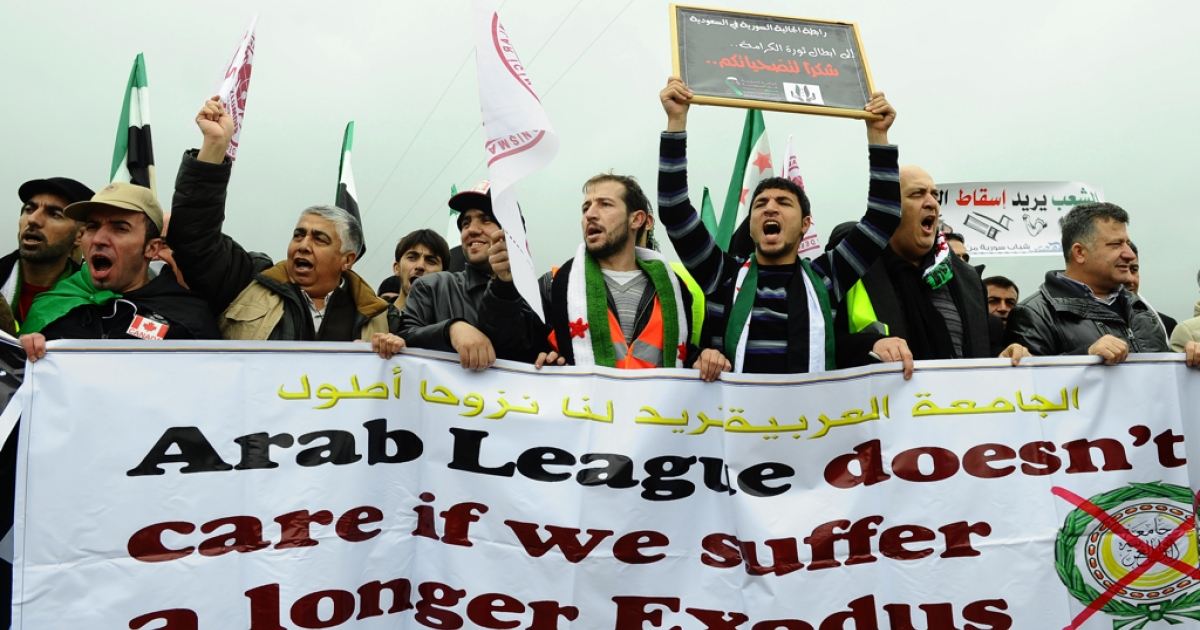 Activists of the Freedom Convoy hold a banner and chant slogans against Syrian President Bashar al-Assad during a gathering on the Turkish-Syrian border.</p>
