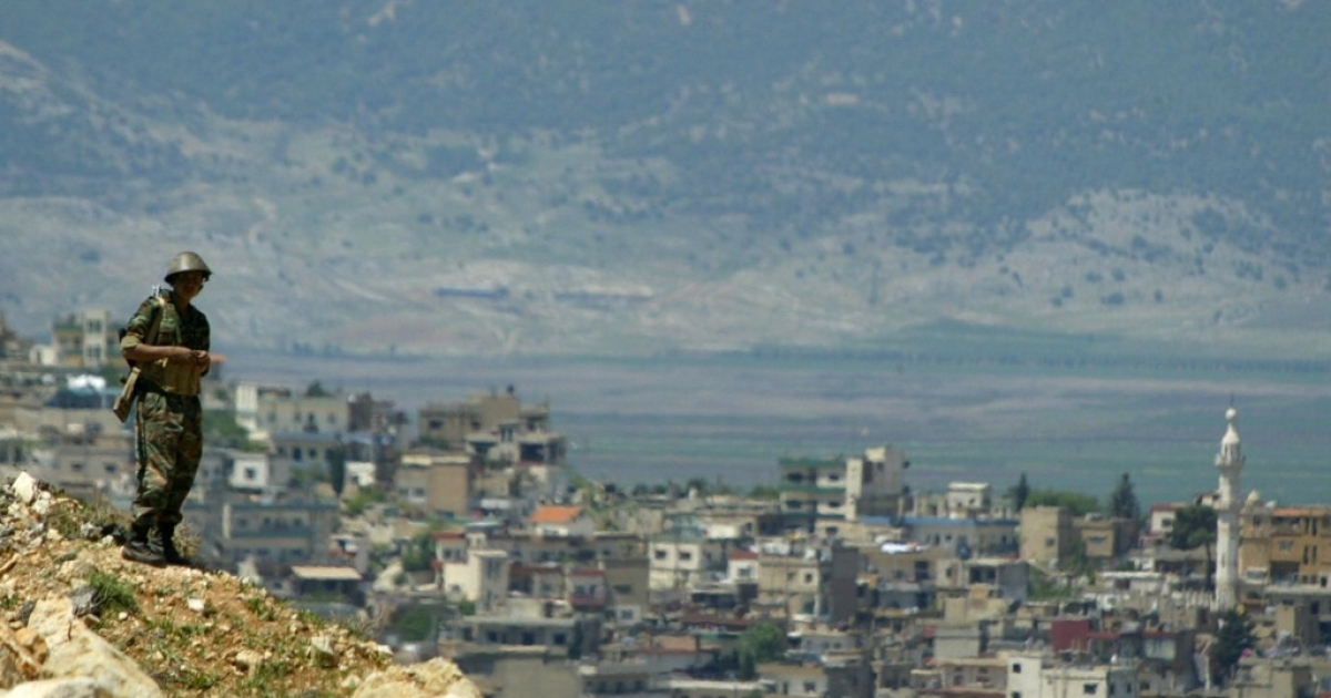 A lone Syrian soldier stands on a hill on the Syrian-Lebanese border. The town of Majdel-Anjar appears in the background.</p>