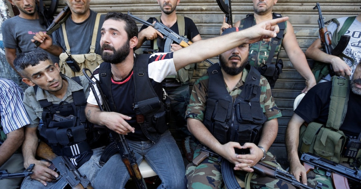 An anti-Damascus regime supporter expresses his anger over the death of a civilian, while his comrades rest from fighting, in the Bab al-Tabbaneh neighbourhood of the northern Lebanese port city of Tripoli, on August 22, 2012.</p>
