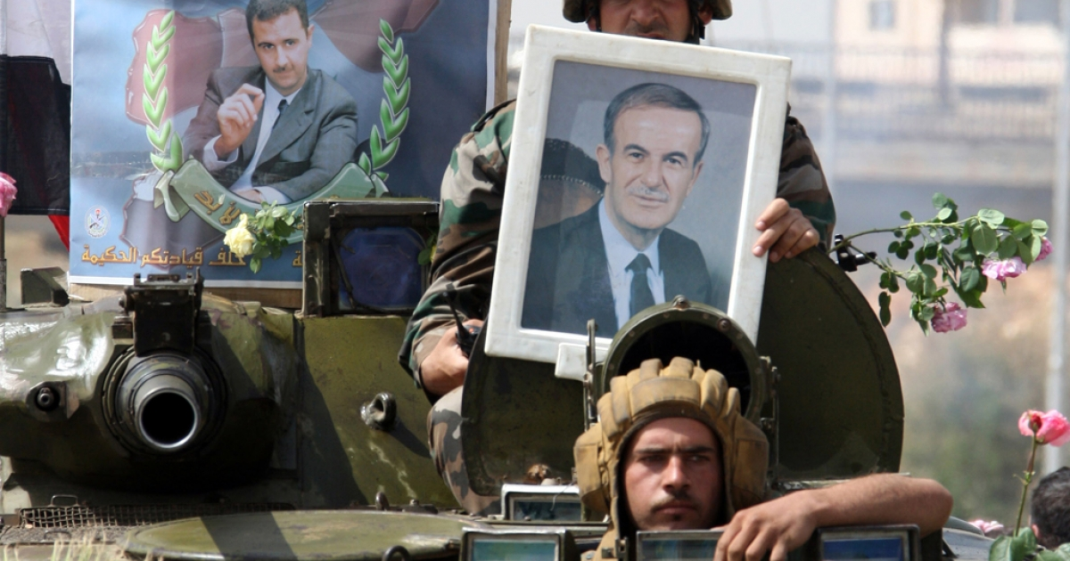 Syrian army troops hold up portraits of President Bashar al-Assad (L) and his late father, former president Hafez al-Assad, as they pull out of the southern protest hub of Daraa after a military lockdown during which dozens of people were killed in what activists termed as