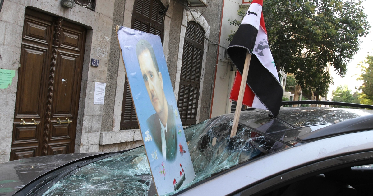 Pro-regime protesters planted the image of President Bashar al-Assad and the Syrian flag through the windscreen of a damaged vehicle as they gathered outside the French Embassy in Damascus on July 11, 2011</p>