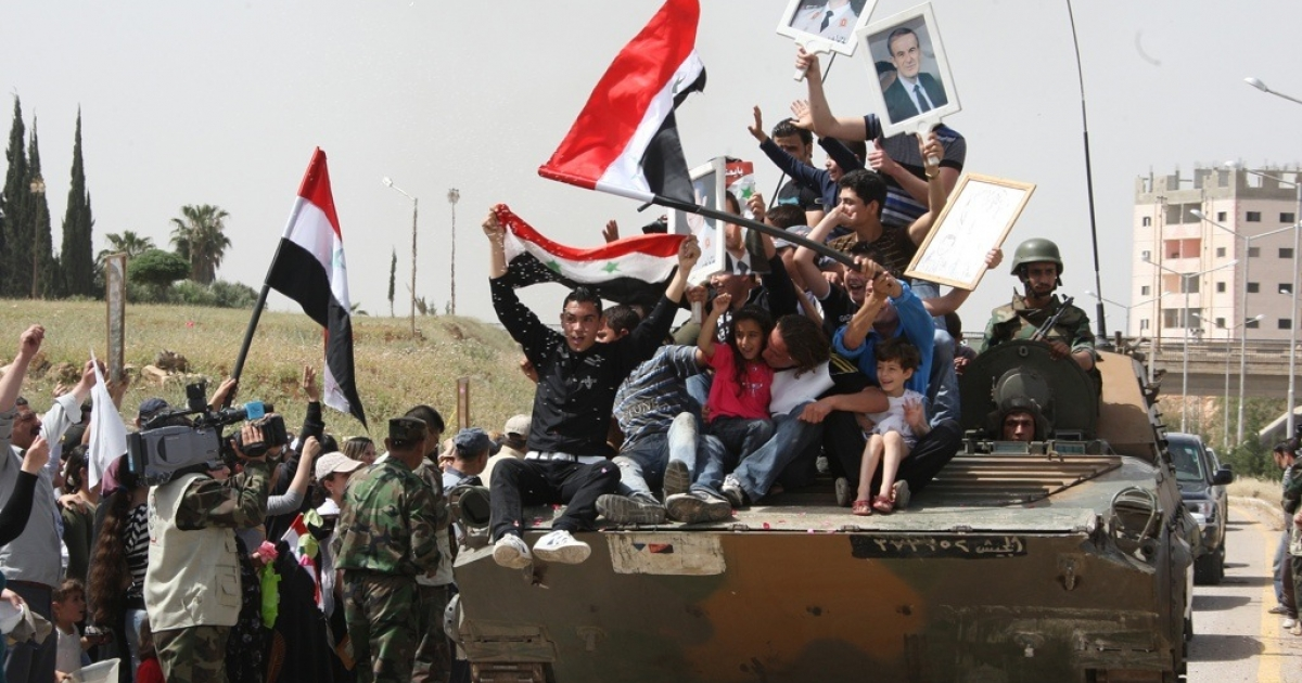 In a photo approved by Syria's government, Syrian youths wave national flags in support of President Bashar al-Assad as they ride on an army personnel carrier.</p>