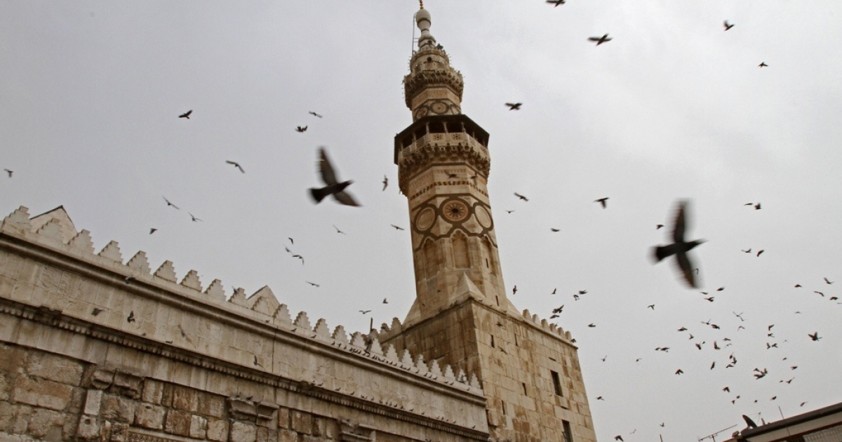 Pigeons fly outside the Omayyad Mosque in Damascus, Syria's capital, on April 2, 2011.</p>