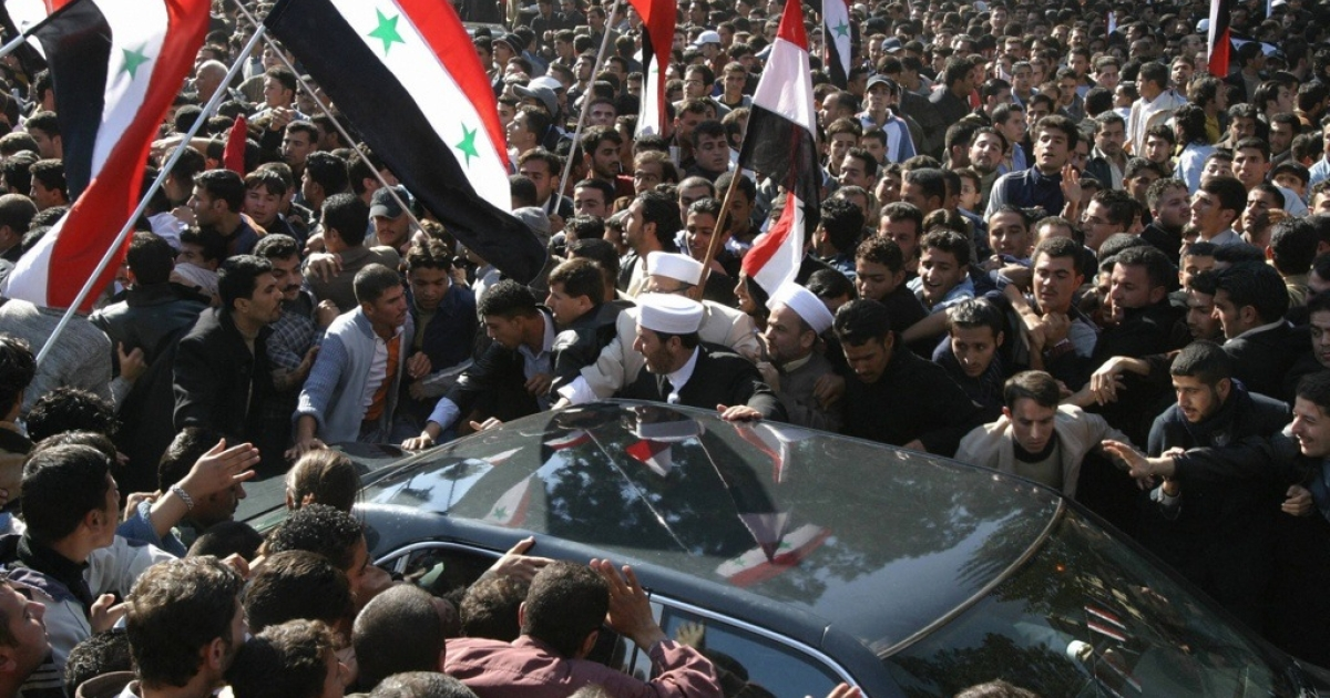 Syrian people gather around the car of their president Bashar al-Assad to greet him after his speech at Damascus University on November 10, 2005.</p>
