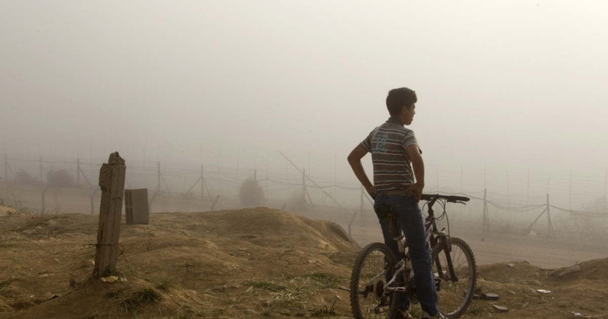 A Druze youth sits on his bicycle as the mist lifts along Israeli's border with Syria, as seen from the Druze village of Majdal Shams, on June 6, 2011.</p>