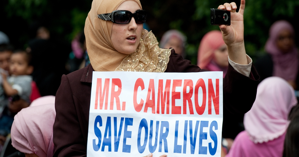 A protestor waves a placard requesting assistance from the UK during a demonstration outside the Syrian embassy in London on May 7, 2011.</p>