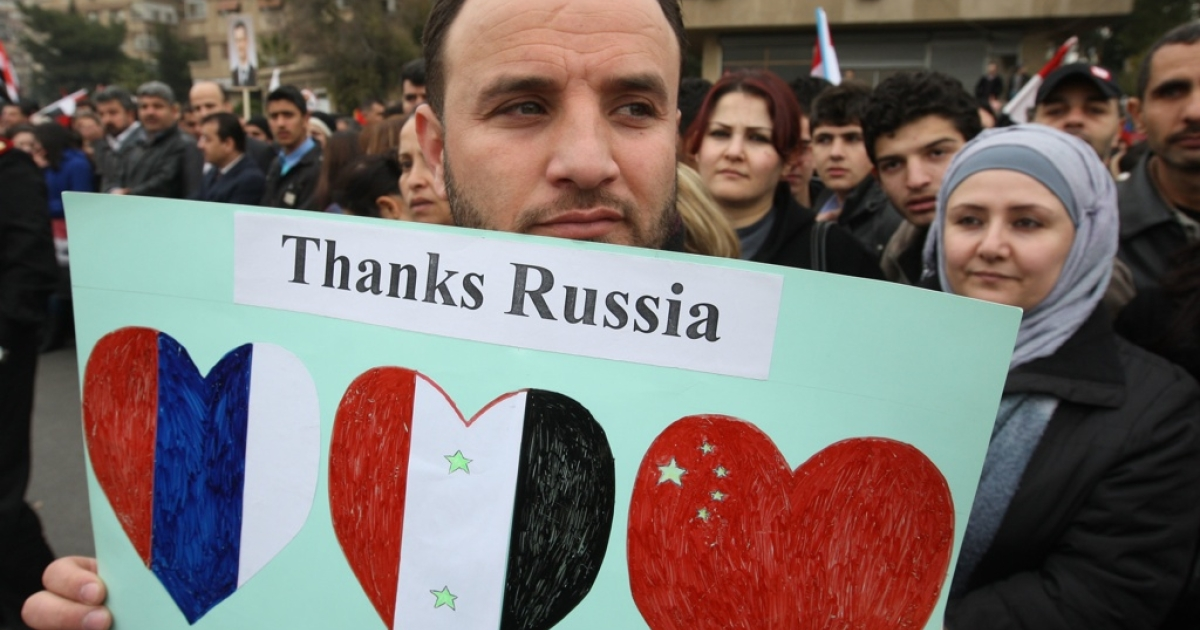 A Syrian pro-government supporter holds up a sign as a convoy carrying Russian Foreign Minister Sergei Lavrov heads toward the presidential palace in Damascus on Feb. 7, 2012.</p>