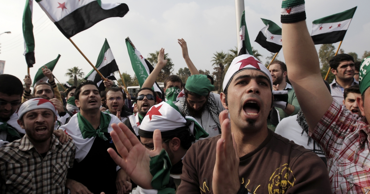 Syria-reform supporters, waving Syria's old pre-Baath national flag, protest outside the Arab League headquarters in Cairo on Nov. 24, 2011.</p>