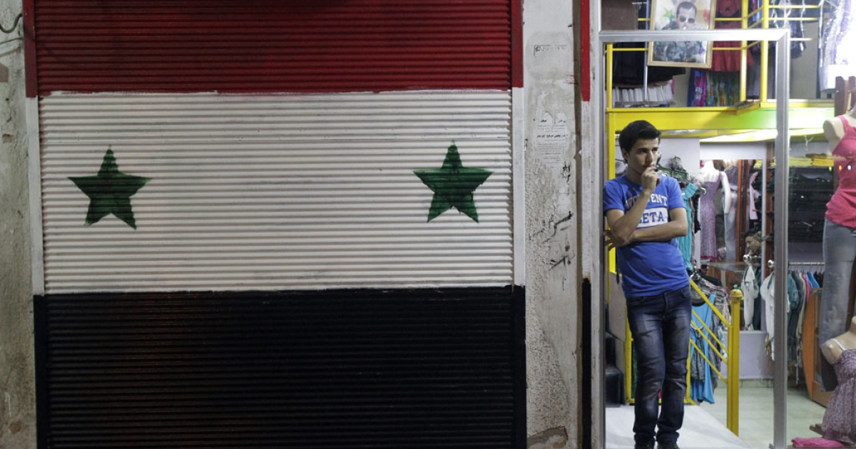 A Syrian vendor stands at the entrance of his shop in the commercial district of the flashpoint city of Homs, northeast of Damascus, on Aug. 29, 2011.</p>