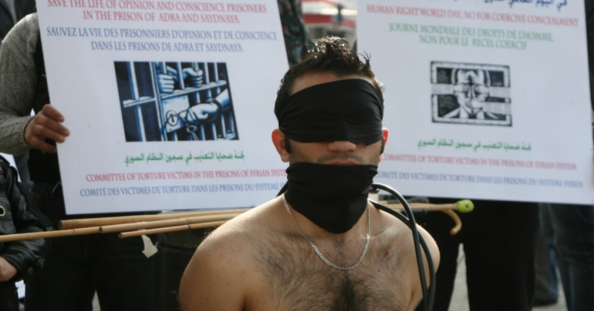 A Syrian protestor mocks being tortured during a sit-in to mark International Human Rights Day, outside the United Nations offices in downtown Beirut on December 10, 2009. The demonstrators were protesting against what they said were torture methods used in Syrian prisons.</p>