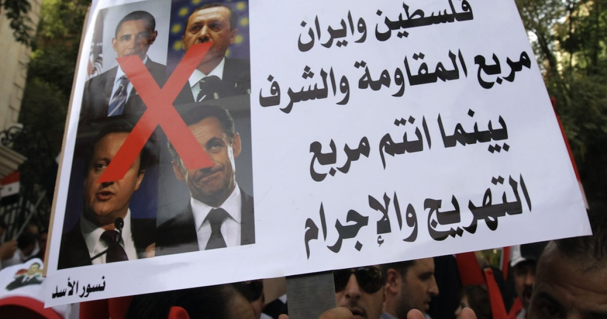 A Syrian protester holds crossed-out pictures of (from top L-R) US President Barack Obama, Turkish Prime Minister Recep Tayyip Erdogan, British Prime Minister David Cameron and French President Nicolas Sarkozy, during a demonstration outside the EU offices in Damascus on September 29, 2011 against new EU sanctions imposed on the pro-government Addounia television channel and five other companies. Arabic writing reads 'Syria, Lebanon, Palestine and Iran are the quartet of resistance and honor. You (referring to above mentioned leaders) are the quartet of clowning and criminality.'</p>
