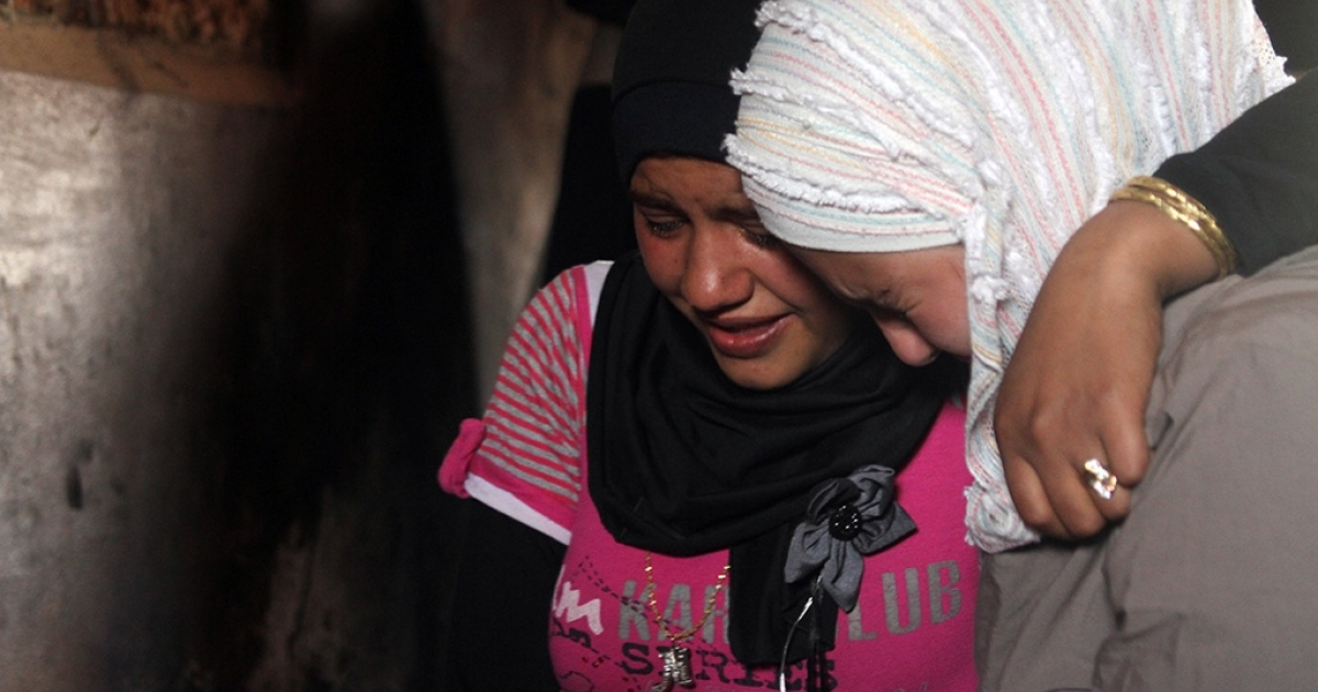 Taimaa and Shimaa Abbous mourn the death of their father after he was killed by tank fire in the village of Deersonpol, Syria. In an earlier attack their home was burned by government forces.</p>