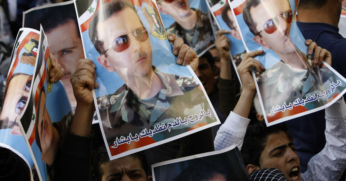 Mainly Syrian workers held up posters of their President Bashar al-Assad as they rallied outside the Syrian embassy in the Lebanese capital Beirut on April 12, 2011.</p>
