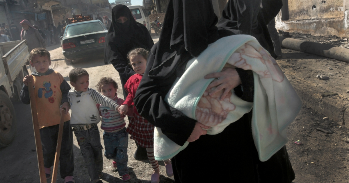 Syrian women and their children flee the violence in the northwestern city of Sermin on March 24, 2012, shortly before government security forces continued bombing the city.</p>