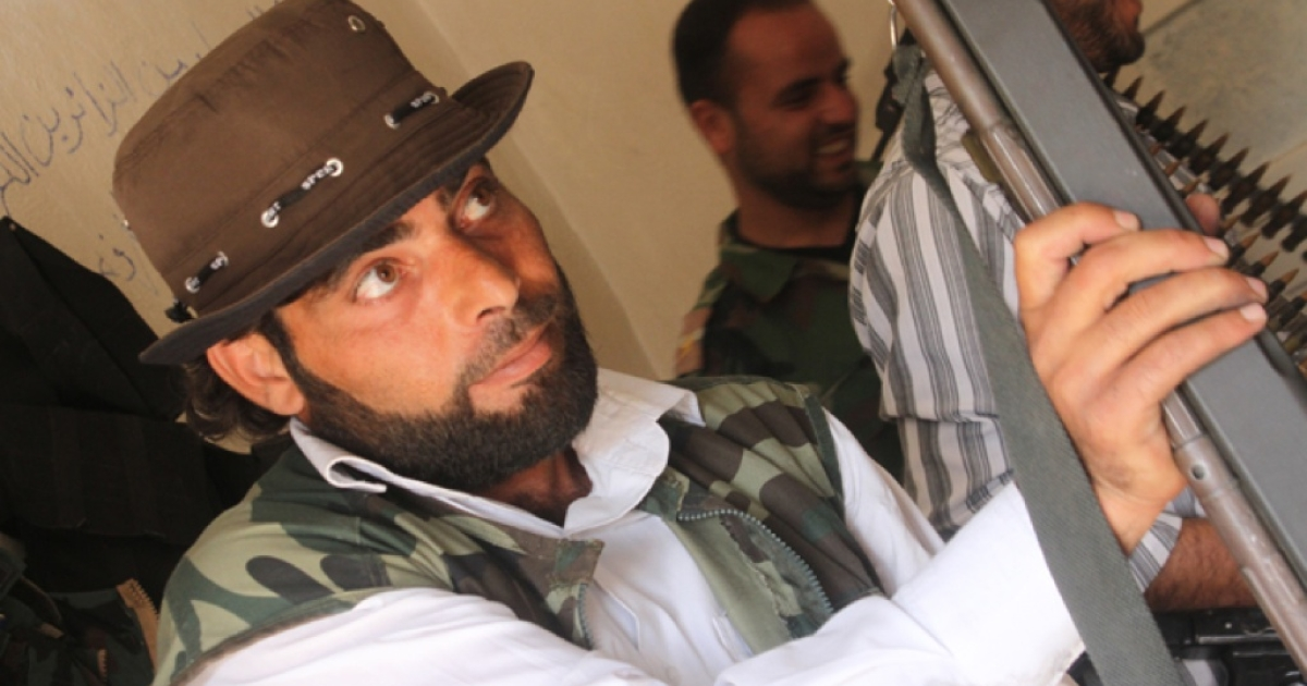 Abu Ibrahim, a Free Syrian Army rebel, examines a new gun purchased from corrupt regime officials at the Al Muhajereen Wal Ansar rebel base in Jabal al-Zawiya.</p>