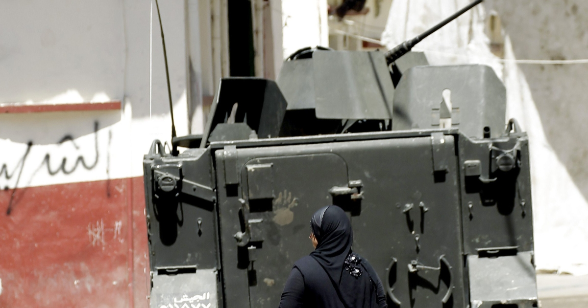 A woman walks behind Lebanese army commandos driving an armored personnel carrier in the Lebanese northern port city of Tripoli on August 23, 2012. Violence in Syria has spilled over into neighboring Lebanon, despite a truce to halt days of violence between pro- and anti-Damascus gunmen.</p>