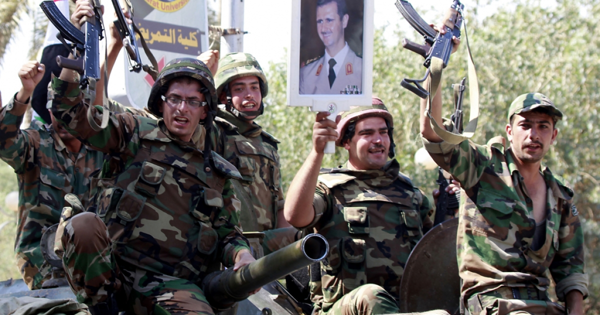 THIS PICTURE WAS TAKEN ON A GUIDED GOVERNMENT TOUR<br />Syrian soldiers raise their weapons while holding a picture of Syrian President Bashar al-Assad as they leave the eastern city of Deir Zor following a 10-day military operation on August 16, 2011. Syria has repeatedly said it is battling