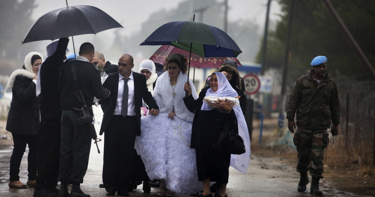 An Israeli army officer (L) welcomes Mayanda Abud (C-R), a 27-year-old Syrian Druze bride from Damascus and her 30-year-old groom Munjed Awad (C-L) as they cross the Syrian-Israel border pass of Quneitra in the Israeli-occupied Golan Heights on November 3, 2011. Mayanda Abud left her family in Syria and entered to the strategic plateau that Israel captured from Syria in the 1967 Six Day War to get married with Munjed Awad who lives in the Israeli control Area. The passage was facilitate by the International Committee of the Red Cross.</p>
