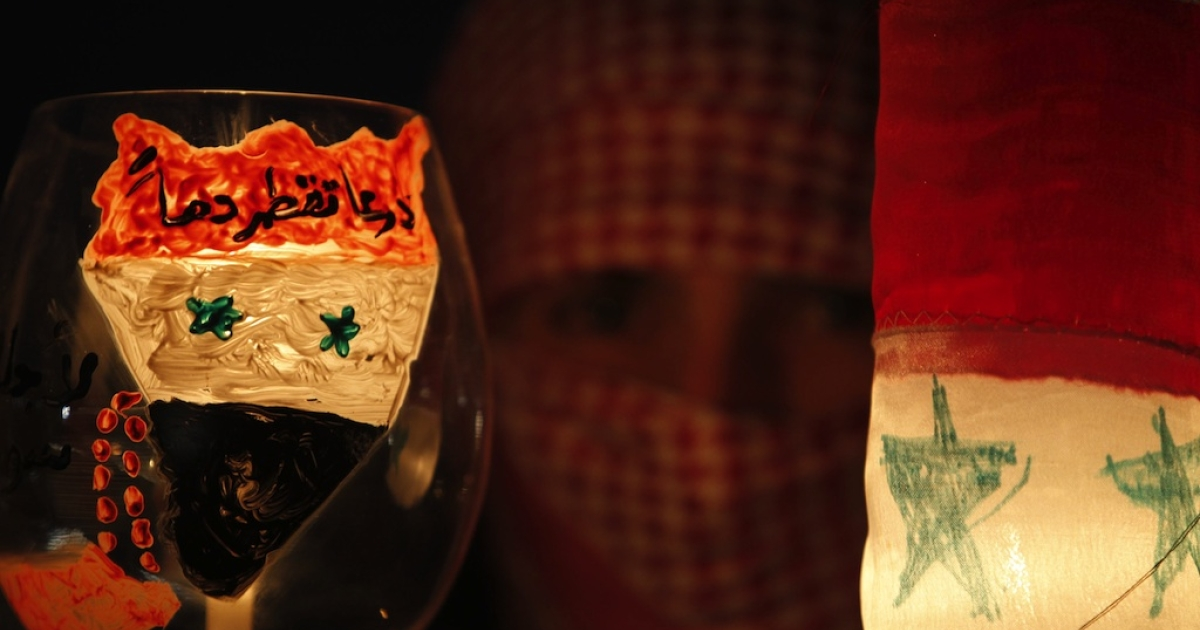 Syrians living in Jordan hold candles during a protest in front of the Syrian Embassy in Amman on April 9, 2011.</p>