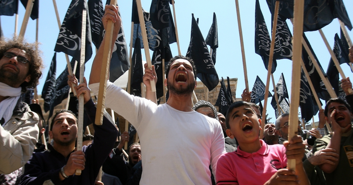 Supporters of pan-Islamic group Hizb al-Tahrir (Party of Liberation) wave the party's flags as they shout slogans during a protest against the Syrian regime in the northern Lebanese city of Tripoli on April 22, 2011.</p>