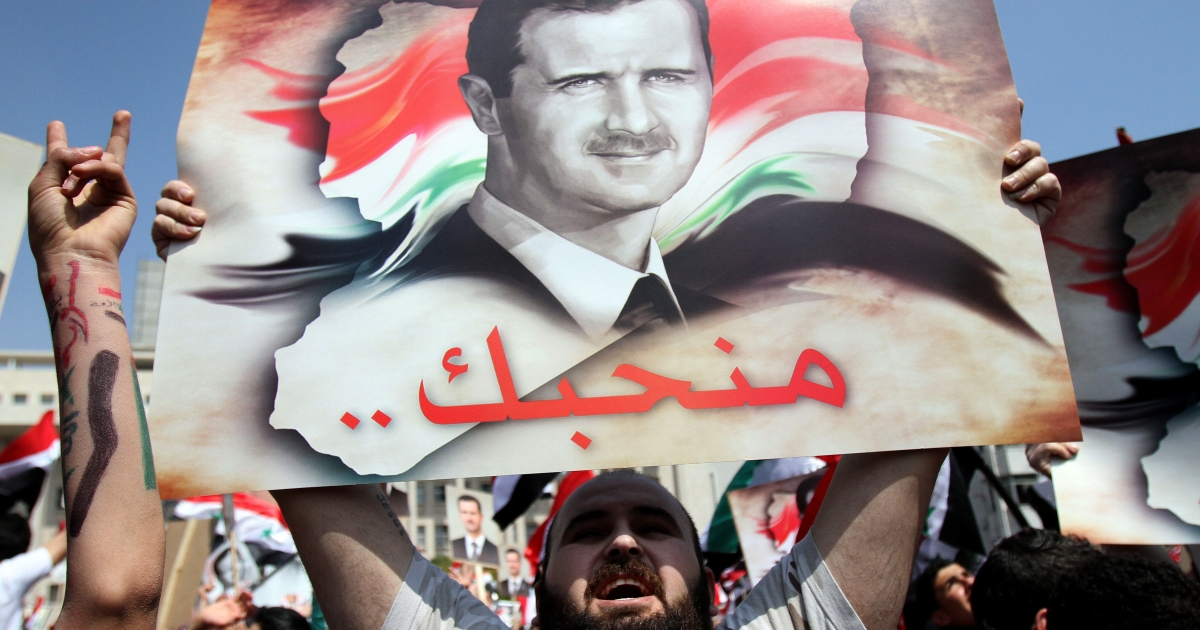 Syrians chant slogans as they rally to show their support for President Bashar al-Assad (portrait), who is facing unprecedented domestic pressure amid a wave of dissent, in Damascus on March 29, 2011.</p>
