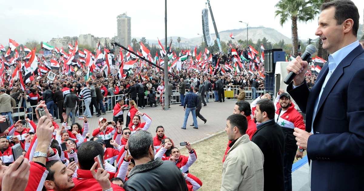 Syria's President Basar al-Assad makes an appearance at a rally with his supporters.</p>