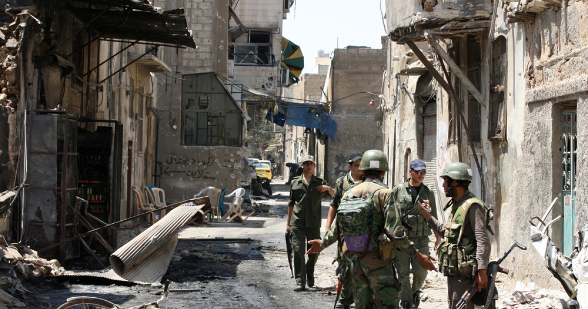 Syrian army soldier walk in a partially destroyed neighborhood in the Midan area in Damascus on July 20, 2012. Syrian regime forces routed rebel fighters from the Damascus neighborhood of Midan, Syrian state television reported, saying troops had