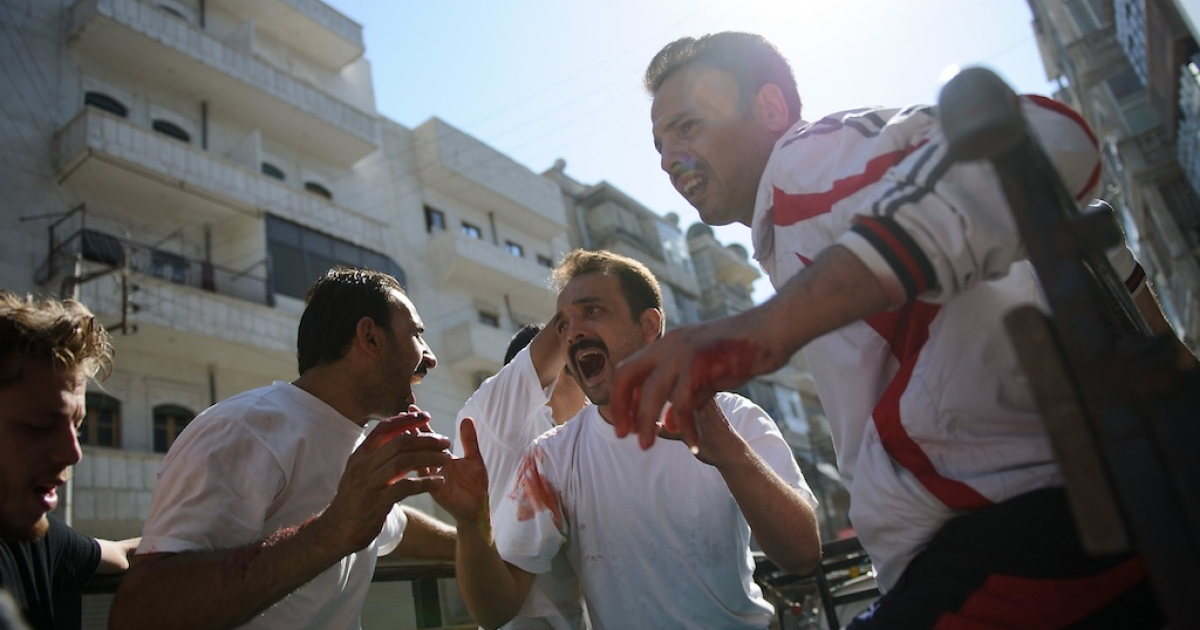 Syrian men mourn the death of a man who was killed by shelling near a bakery in the Tariq al-Bab district of the northern Syrian city of Aleppo on August 10, 2012.</p>