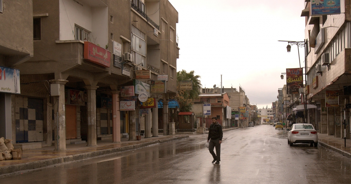 A picture taken under the supervision of Syrian security shows a man walking past closed shops in the southern Syrian city of Daraa, hub for a week of anti-regime protests, on March 24, 2011. Syria, which is still under a 1963 emergency law banning demonstrations, is the latest state in the Middle East to witness an uprising against a long-running autocratic regime.</p>