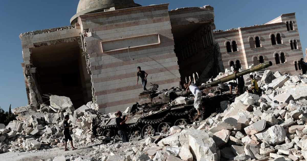 Syrian civilians gather around the remains of an army tank in front of a bombed-out mosque in the northern town of Azaz, some 47km north of Aleppo, on August 23, 2012. Today, Sept. 5, 2012, unconfirmed footage showed the collapse of the minaret of Al-Rashid Mosque in Aleppo, reportedly stuck by Syrian President Bashar al-Assad's forces. This allegation could not be confirmed.</p>
