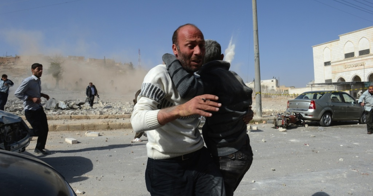 A Syrian man holding a boy runs for cover as a second bomb explodes near the northern Syrian town of Al-Bab, 40 kilometers north-east of Aleppo on Nov. 4, 2012. An AFP correspondent reported three air strikes in close succession on Al-Bab.</p>
