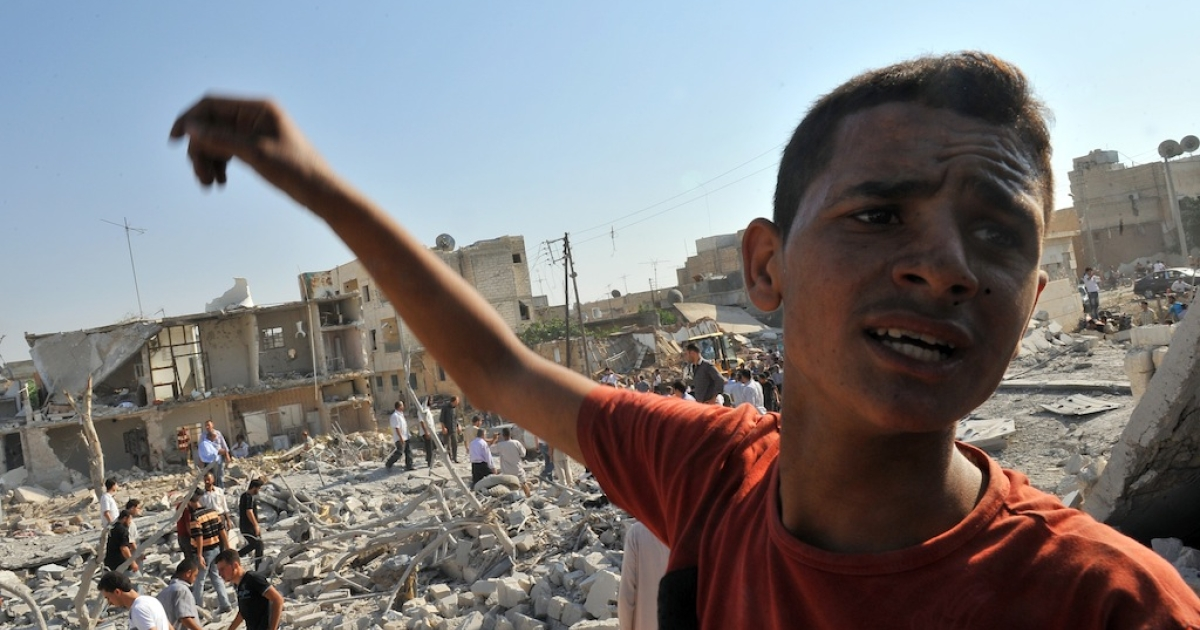 A Syrian boy reacts as they look for people trapped under the rubble following an air strike in the town of Azaaz, near the northern restive Syrian city of Aleppo, on Aug. 15, 2012. UN investigators said the Syrian regime had committed crimes against humanity, as at least 20 people were reported killed in a major air strike in a rebel bastion in the north.</p>