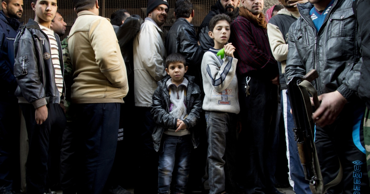 A Syrian opposition fighter keeps the queue in order as people line up to buy bread outside a bakery in the al-Fardos neighbourhood of the northern Syrian city of Aleppo on December 9, 2012.</p>