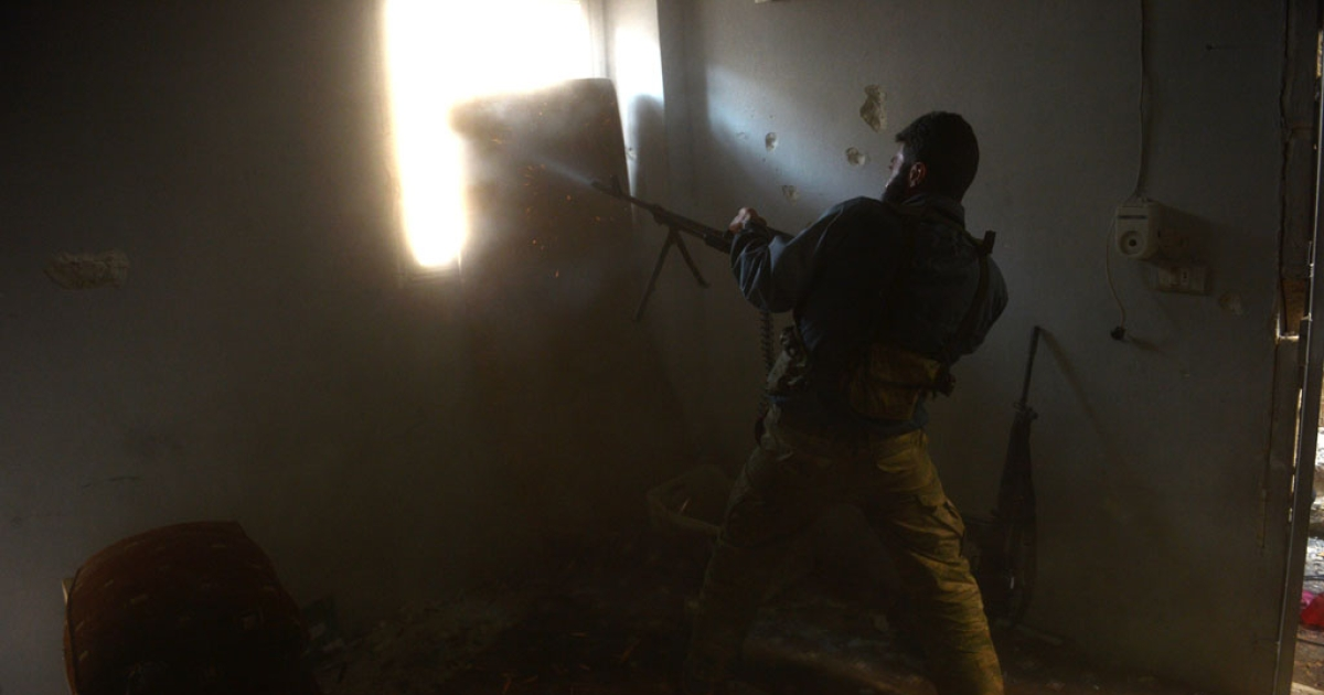 A rebel fires his machine gun against pro-Syrian government forces in the Bustan al-Bashar district of Aleppo on October 27, 2012.</p>