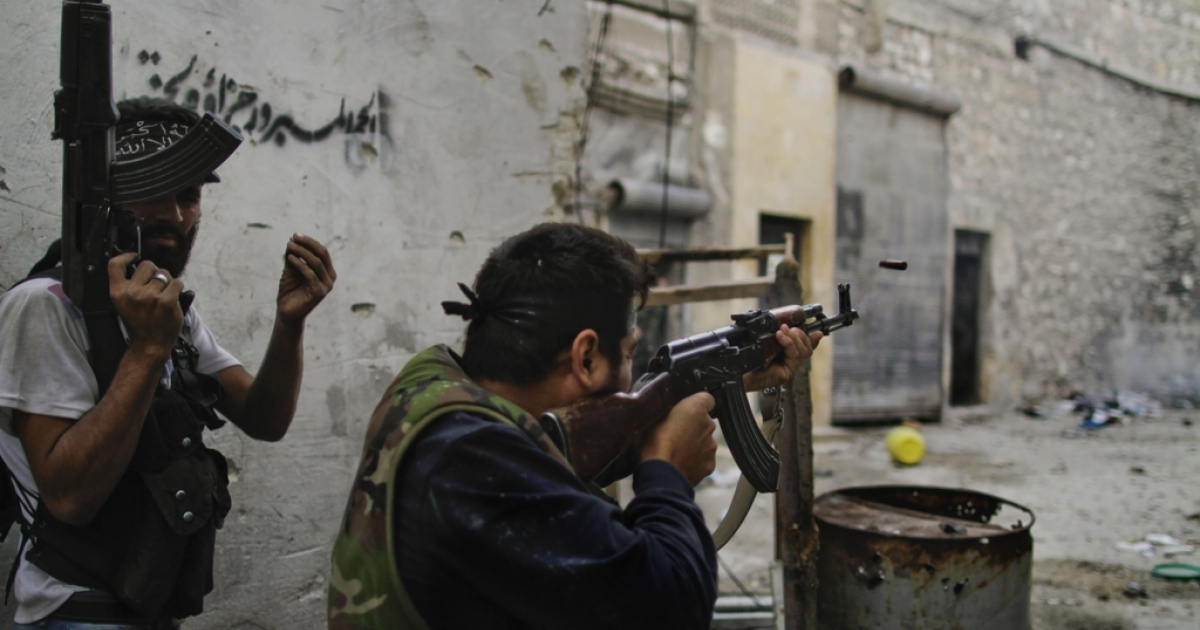 Free Syria Army (FSA) fire towards regime loyalist soldiers during a battle to dislodge a sniper from its position overlooking the two main roads in the neighbourhood of Askar in Syria's northern city of Aleppo on October 24, 2012.</p>