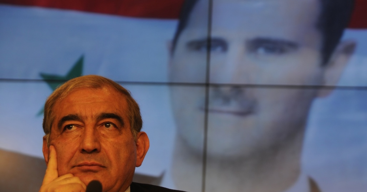Former Syrian deputy premier Qadri Jamil at a press conference in Moscow on August 21, 2012, with a picture of Syrian President Bashar al-Assad in the background.</p>