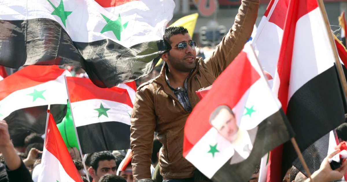 Syrian flags are waved as people take to the streets after voting on a new constitution that could end five decades of single-party domination, in the capital Damascus, on February 26, 2012, although the opposition has called a boycott as the regime's bloody crackdown shows no sign of easing.</p>