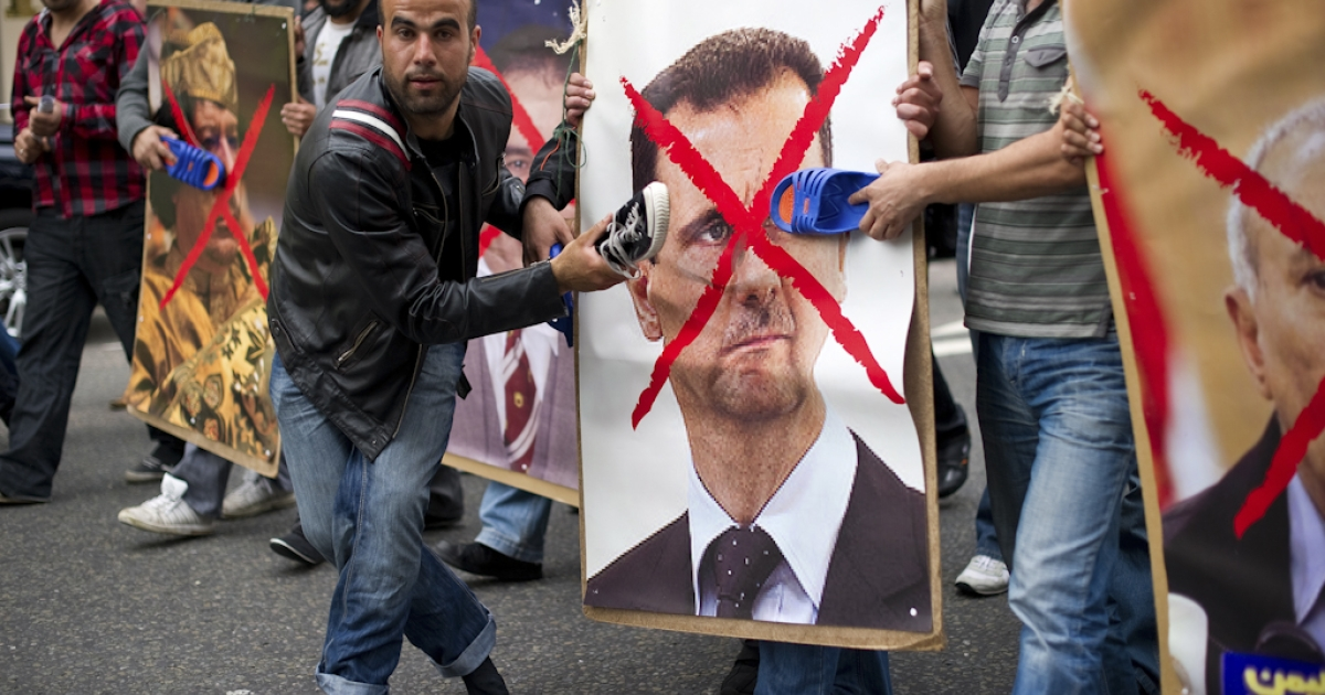 Protestors hit posters of Syria's President Bashar al-Assad (R) and Liya's Colonel Gadaffi with shoes during a demonstration outside the Syrian embassy in London on May 7, 2011. The demonstration was called to show support for the uprising in Libya, Syria, Bahrain and Yemen</p>