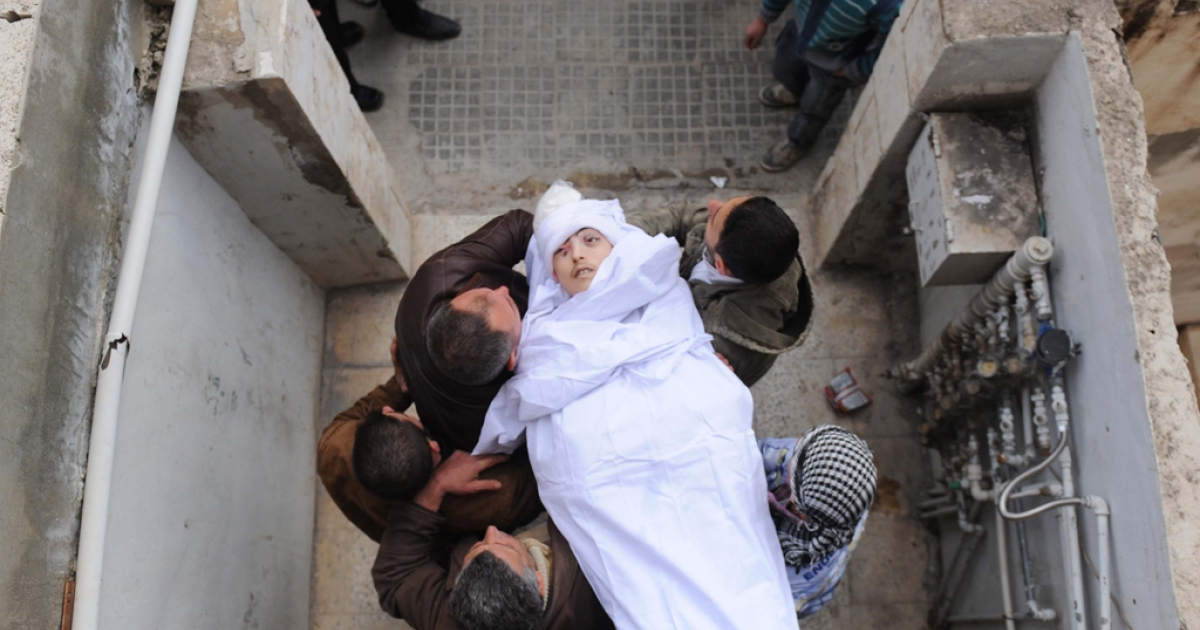 Syrians carry the body of a man reportedly killed in violence in the northwestern Idlib region on February 23, 2012. A UN report released on the same day accused Syrian government and army officials of crimes against humanity.</p>
