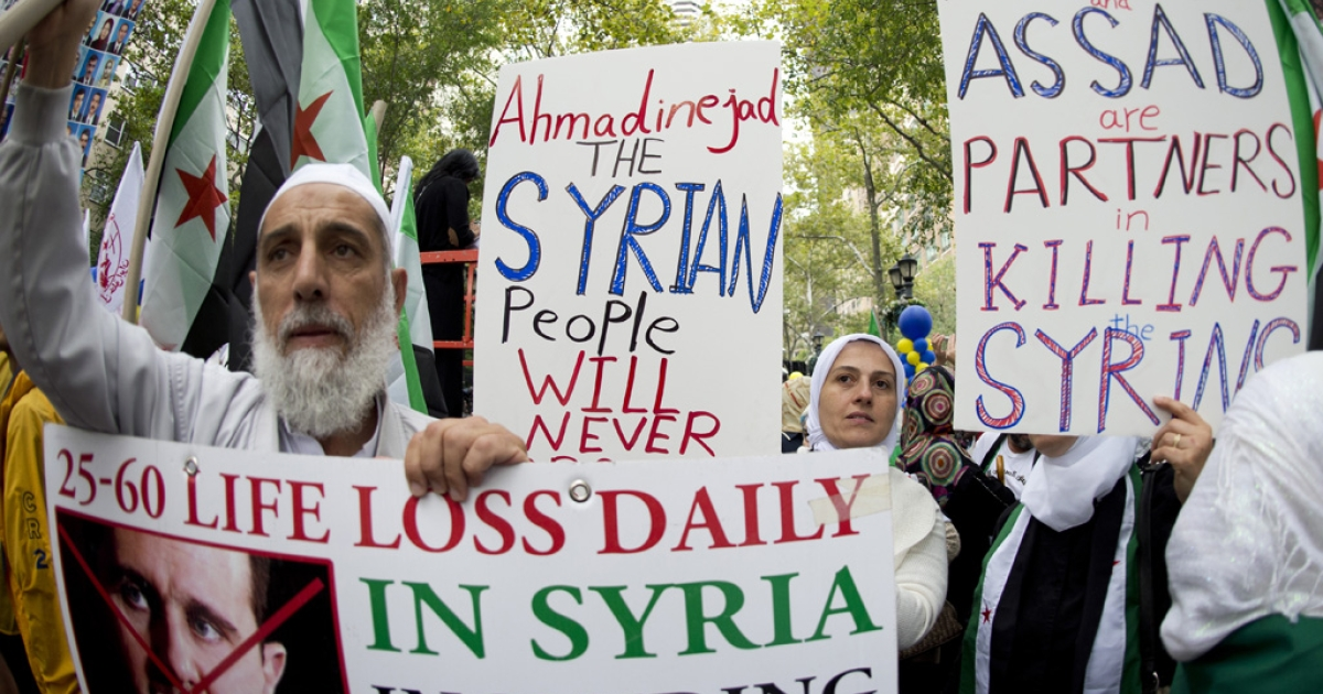Demonstrators protest against Iran's President Ahmadinejad and Syria's President Bashar al-Assad during the 67th United Nations General Assembly meeting, September 26, 2012 in New York.</p>